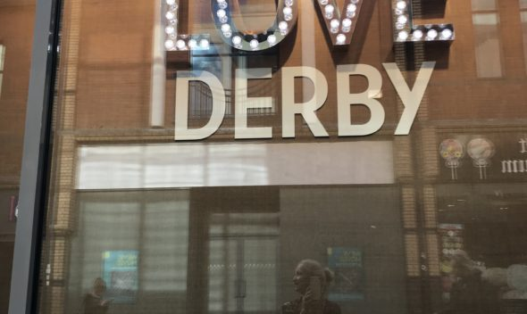 photo of the sign on a building that says 'love derby'